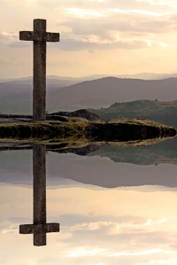 stone cross in mountain at sunset and reflection in water