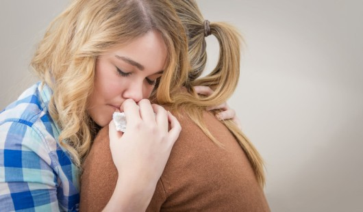 Closeup on sad teen daughter crying by problems in the shoulder of her mother. Mother embracing and consoling daughter.